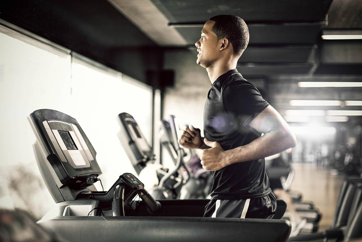 Healthy young man in GYM running on treadmill