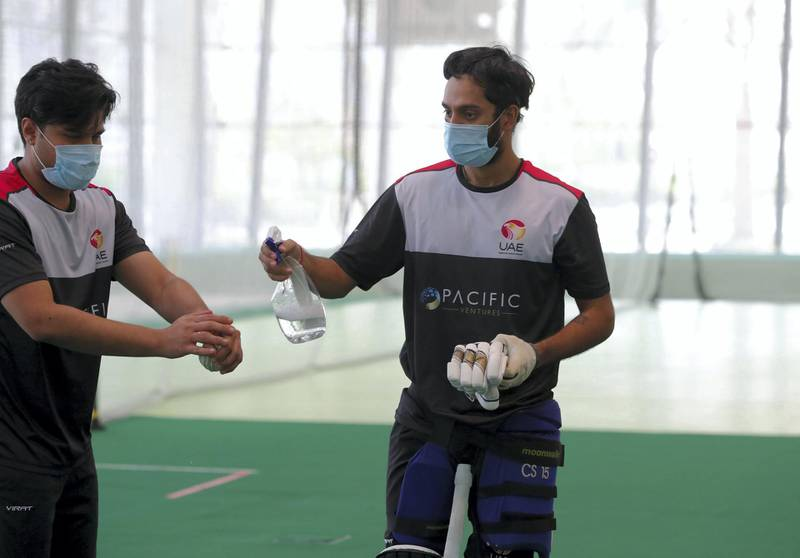Dubai, United Arab Emirates - Reporter: Paul Radley. Sport.  Chirag Suri and Imran Haider disinfect the ball. The UAE cricket team are back at training at the ICC academy after the government have eased restrictions due to Coivd-19/Coronavirus. Sunday, June 7th, 2020. Dubai. Chris Whiteoak / The National