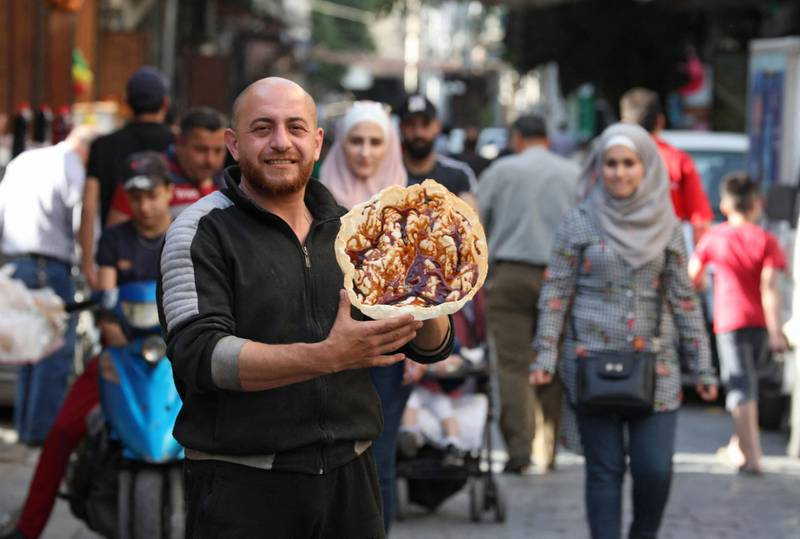 """A Syrian vendor displays the traditional sweet known as """"al-Naem"""", commonly served during the Muslim holy month of Ramadan, in Damascus' Shaqhoor neighbourhood on April 28, 2021. Year after year Ramadan meals become more frugal in war-torn Syria as the economy worsens, but Damascus dwellers say a traditional wafer-thin crispy pancake called """"naaem"""" is there to stay. During the Islamic fasting month, Damascus residents flock just before sundown to buy the deep-fried sweet from ambulant sellers making them in bubbling cauldrons all over the sidewalks. The crunchy pastry -- also called """"Ramadan bread"""" -- is prepared by dropping a thin circle of dough into hot oil until it snaps like a crisp. / AFP / LOUAI BESHARA"""