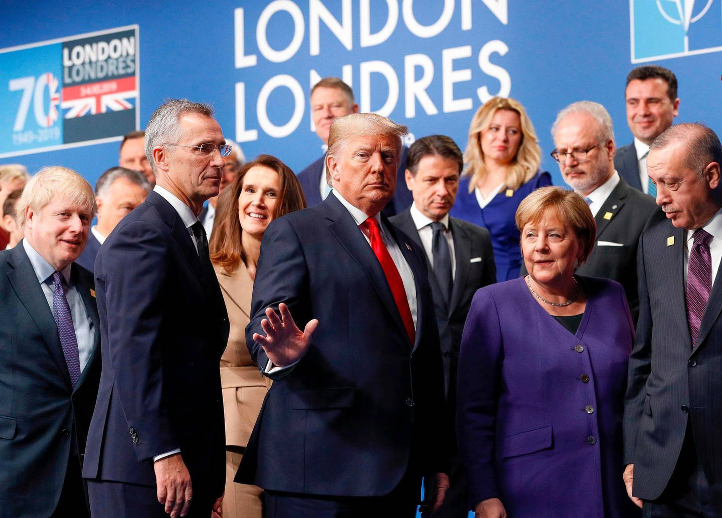 Britain's Prime Minister Boris Johnson (L), US President Donald Trump (C), German Chancellor Angela Merkel (2R), Turkey's President Recep Tayyip Erdogan (R) and other NATO leaders leave the stage after the family photo to head to the plenary session at the NATO summit at the Grove hotel in Watford, northeast of London on December 4, 2019. / AFP / POOL / PETER NICHOLLS