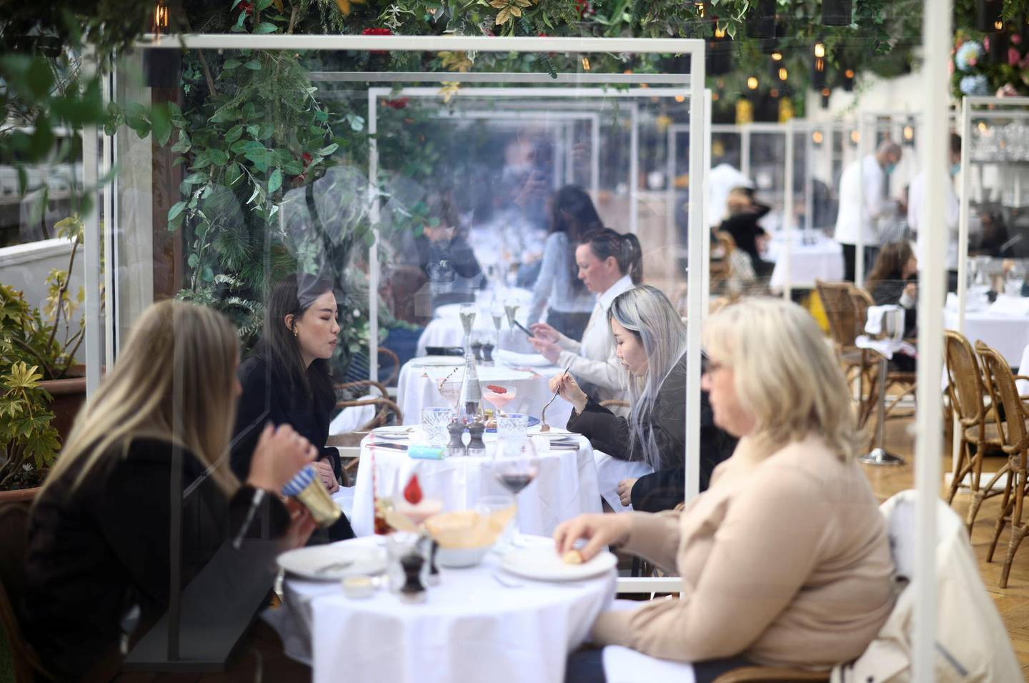 People sit in a restaurant on the roof of the Selfridges department store on Oxford street, as the coronavirus disease (COVID-19) restrictions ease, in London, Britain April 12, 2021. REUTERS/Henry Nicholls