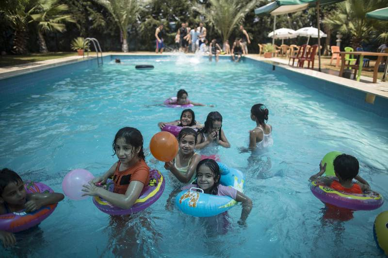 Palestinians spend time at the pool in Gaza City on July 24, 2017. Around 95 percent of Gaza's groundwater is unsuitable for human consumption. There are few public pools to cool down, while many houses have little water.  / AFP PHOTO / MAHMUD HAMS