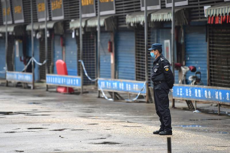 A security guard stands outside the Huanan Seafood Wholesale Market where the coronavirus was detected in Wuhan on January 24, 2020 - The death toll in China's viral outbreak has risen to 25, with the number of confirmed cases also leaping to 830, the national health commission said. (Photo by Hector RETAMAL / AFP)