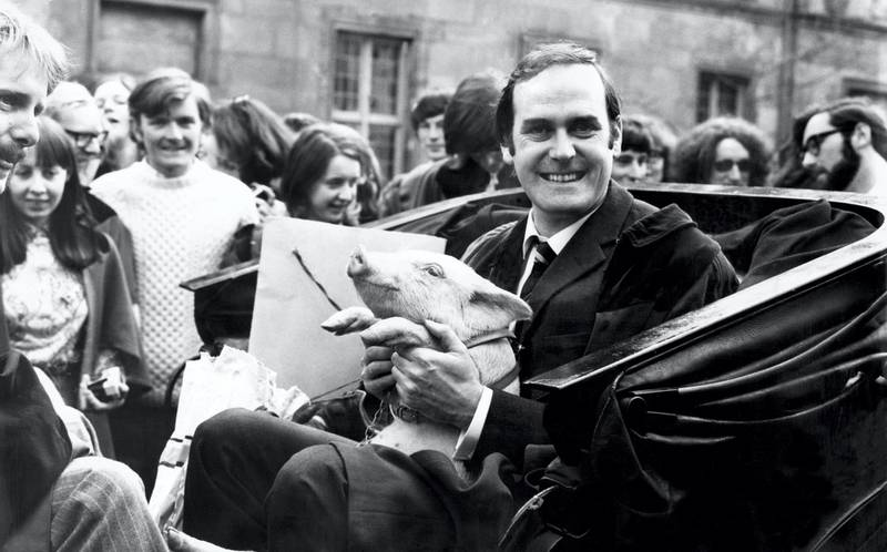 John Cleese at St Andrews ready for a drive around with a piglet. From 1970 to 1973, Cleese served as rector of the University of St Andrews, Fife, Scotland. John Cleese was given the eight week old piglet, by David Steel (Gatehouse of Fleet) and Ronald Sanderson (East Lothian) on behalf of the Porker Club. 20th April 1971. (Photo by Daily Record/Mirrorpix/Mirrorpix via Getty Images)