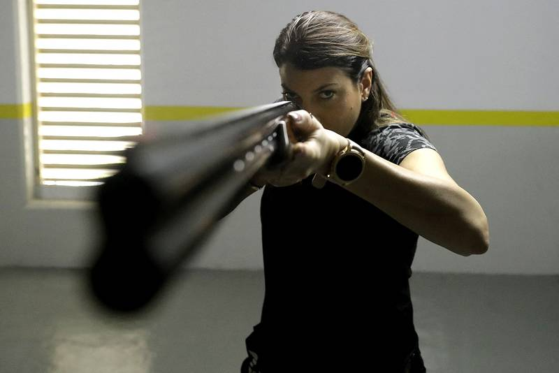 Lebanese trap shooter Ray Bassil trains for this summer's Olympics in her underground parking in Sahel Alma near the coastal city of Jounieh, north of the capital Beirut, on February 5, 2021. - Determined to stay fit despite the coronavirus pandemic, the 32-year-old turned the parking spaces under her apartment block into a virtual firing range, all without shooting a single round.Bassil herself had fallen ill from Covid-19, but sprang back into training despite the round-the-clock curfew. (Photo by JOSEPH EID / AFP)
