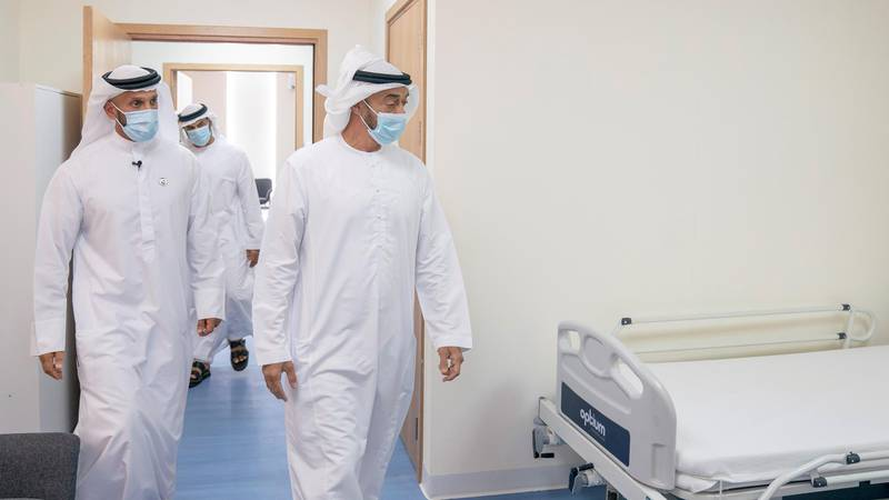 ABU DHABI, UNITED ARAB EMIRATES - May 18, 2020: HH Sheikh Mohamed bin Zayed Al Nahyan, Crown Prince of Abu Dhabi and Deputy Supreme Commander of the UAE Armed Forces (R) visits Emirates Field Hospital, at Emirates Humanitarian City. Seen with HE Sheikh Abdullah bin Mohammed Al Hamed, Chairman of the Department of Health - Abu Dhabi (L).  ( Hamad Al Mansoori for the Ministry of Presidential Affairs ) ---