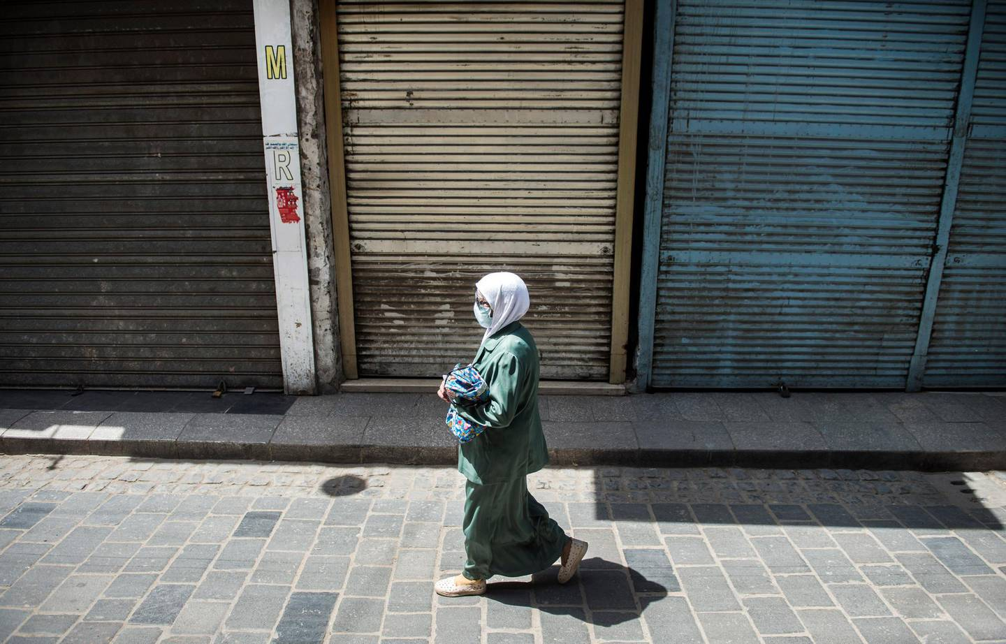 epa08340838 A woman wearing face mask walks in front of closed shops, in Cairo, Egypt, 03 April 2020. Egyptian authorities have imposed a two-week-long curfew, starting on 25 March, during which all public transportation in the city is suspended due to the ongoing pandemic of the Covid-19 disease caused by the SARS-CoV-2 coronavirus.  EPA/Mohamed Hossam