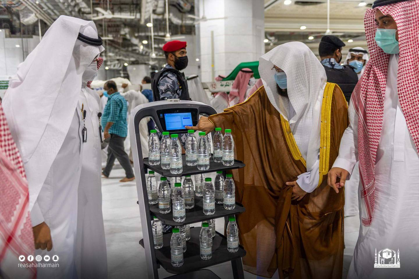 General President of the Affairs of the Grand Mosque and the Prophet's Mosque Abdul-Rahman Al-Sudais with robots serving Zamzam water bottles at the Grand Mosque in Makkah on Saturday. SPA