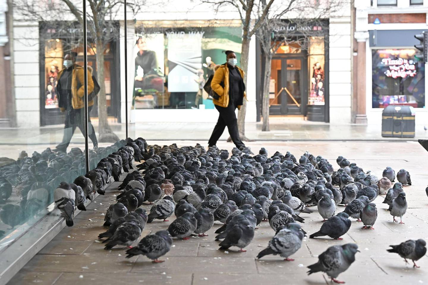 Pidgeons gather outside the shuttered entrance to a John Lewis department store, closed down due to lockdown restrictions, on an empty Oxford Street as Britain enters another national lockdown in London on January 5, 2021. England's six-week lockdown, which began at midnight, emulates the first national coronavirus curbs in place from March to June -- but goes further than another instituted in November when schools remained open. Authorities in Wales, Scotland and Northern Ireland have all taken similar measures, putting the UK as a whole in lockdown.  / AFP / JUSTIN TALLIS