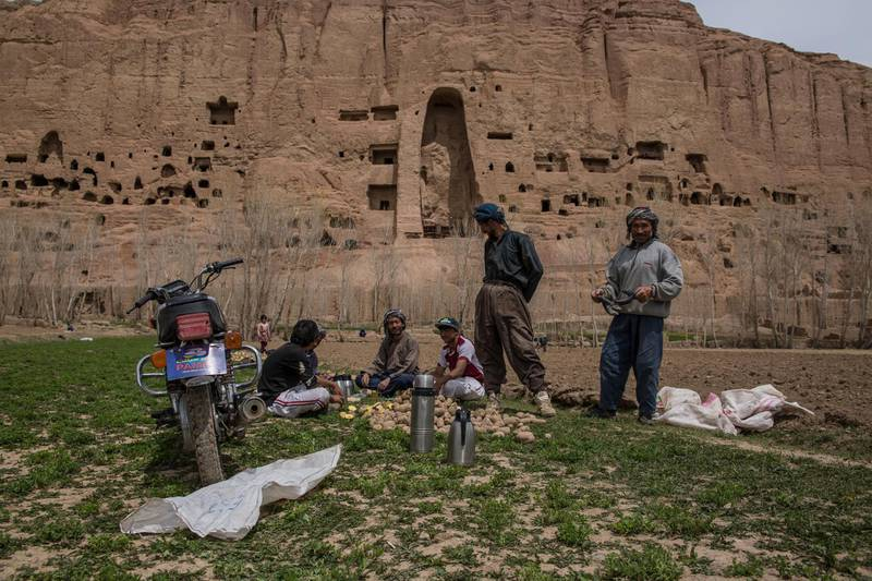 Potato farmers take a break from planting potatoes in Bamyan city; the remains of the Buddha statues in the background, blown up by the Taliban in 2001.