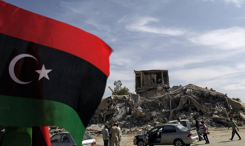 """(FILES) In this file photo taken on November 1, 2011, Libyans arrive to inspect the remains of the destroyed """"Beit al-Samed"""" or """"The Resisting House"""", as dubbed by slain leader Moamer Kadhafi, in his Bab al-Aziziya compound after it was bombed by the US in 1986. Before Moamer Kadhafi's ouster Libyans avoided like the plague the Bab al-Aziziya compound from where the dictator ruled, but a housing shortage in Tripoli has forced squatters to move in. / AFP / JOSEPH EID"""