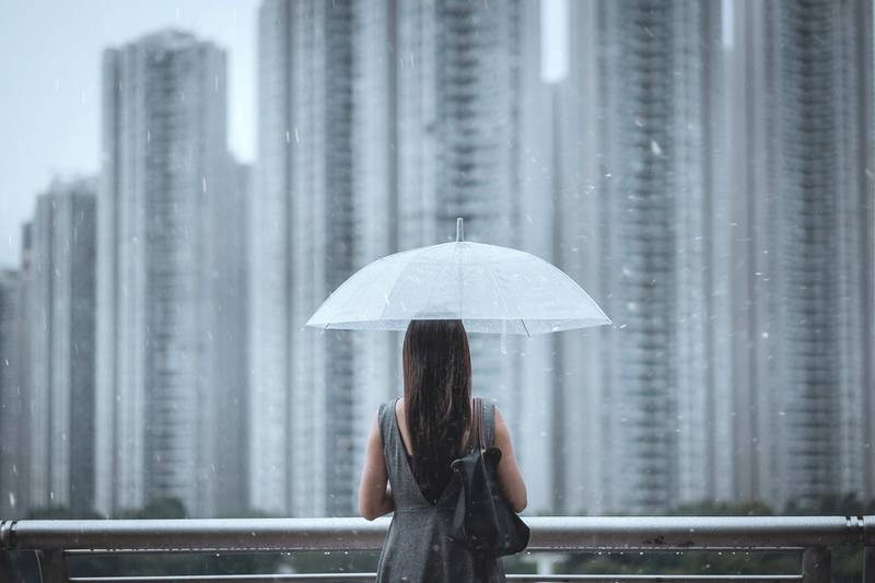 Rear view of young businesswomen with umbrella overlooking the city on a rainy and gloomy day, with blurry highrise residential blocks in the background.