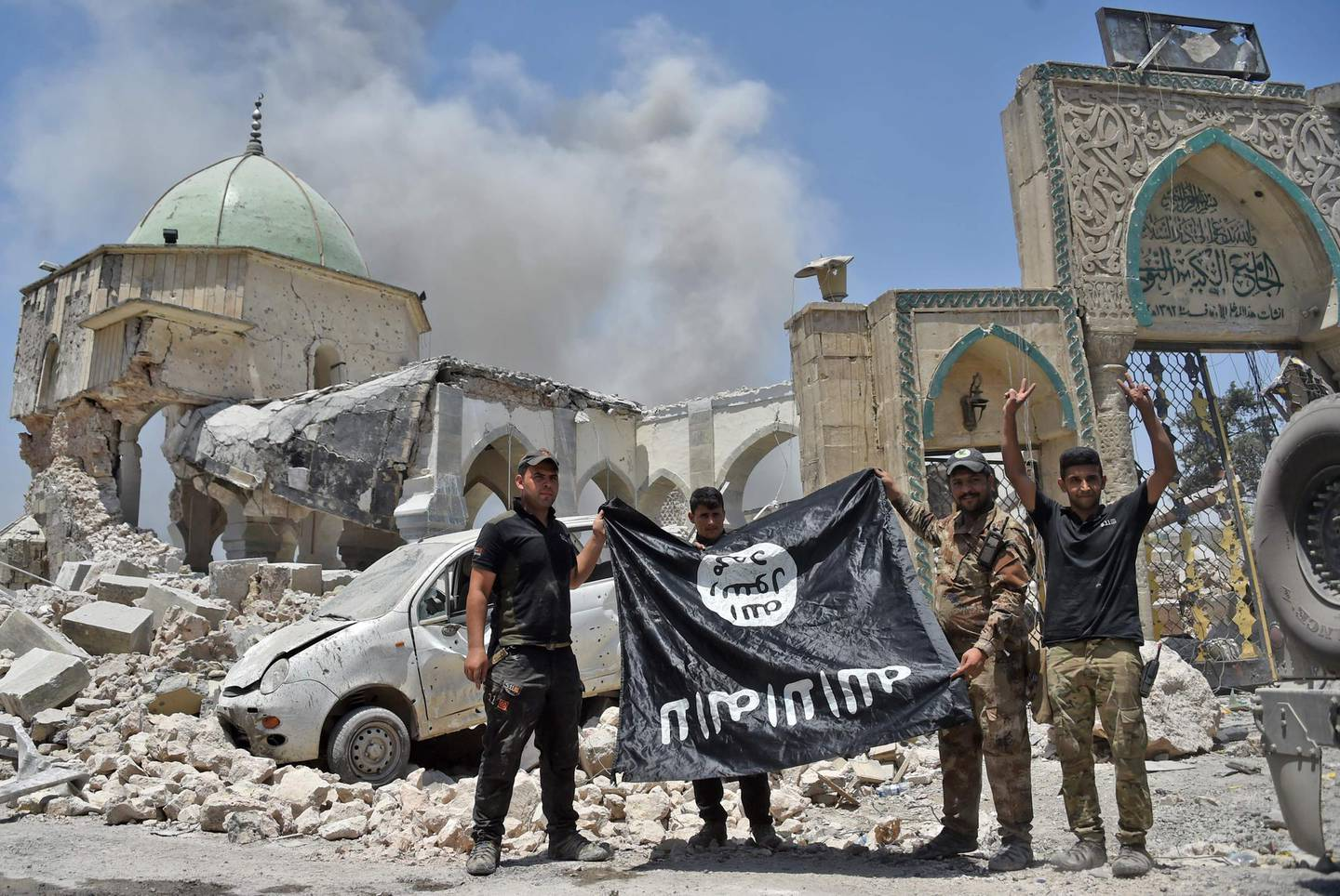 """(FILES) In this file photo taken on June 30, 2017, members of the Iraqi Counter-Terrorism Service (CTS) with a flag of the Islamic State held upside-down, outside the destroyed Al-Nuri Mosque in the Old City of Mosul, after the area was retaken from IS. Even as the last pockets of resistance in eastern Syria hold their ground, the Islamic State group is shapeshifting into a new, but no less dangerous, underground form, experts warn. Also known as ISIS, or the Islamic State in Iraq and Syria, it had long been ready to cede the territory it once held in its self-styled """"caliphate,"""" and has already begun the switch to a more clandestine role, closer to its roots.  / AFP / FADEL SENNA / TO GO WITH AFP STORY by Michel MOUTOT, """"Islamic State not defeated, just transforming, experts say"""""""