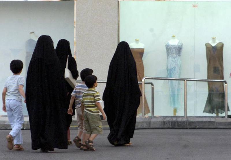 Saudi women, wearing chadors outdoors in line with the strict Islamic dress code in the kingdom, pass with their children a women's boutique in Saudi Arabia's Red Sea port of Jeddah 25 September 2002. Most Gulf women my be covered from head to toe, but the staggering 1.7 billion dollars spent annually in the region on beauty products reveal they are pretty coquettish.   AFP PHOTO/Mahmoud MAHMOUD (Photo by MAHMOUD MAHMOUD / AFP)