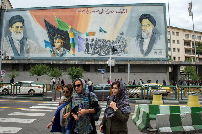 Women cross a street near a giant political mural depicting Ayatollah Ali Khamenei, Iran's supreme leader, left, and Ruhollah Khomeini, founder of the Islamic republic of Iran, in Tehran, Iran, on Wednesday, May 9, 2018. U.S. President Donald Trump pulled out of the 2015 deal that put limits on Iran's nuclear program in exchange for rapprochement with the West. Photographer: Ali Mohammadi/Bloomberg