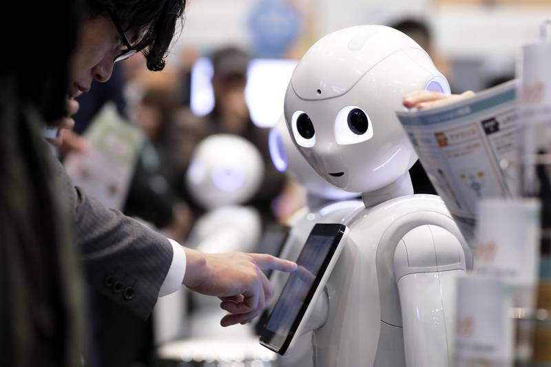 An attendee tries out an application on a SoftBank Group Corp. Pepper humanoid robot at the SoftBank Robot World 2017 in Tokyo, Japan, on Tuesday, Nov. 21, 2017. SoftBank Chief Executive Officer Masayoshi Son has put money into robots, artificial intelligence, microchips and satellites, sketching a vision of the future where a trillion devices are connected to the internet and technology is integrated into humans.  Photographer: Kiyoshi Ota/Bloomberg