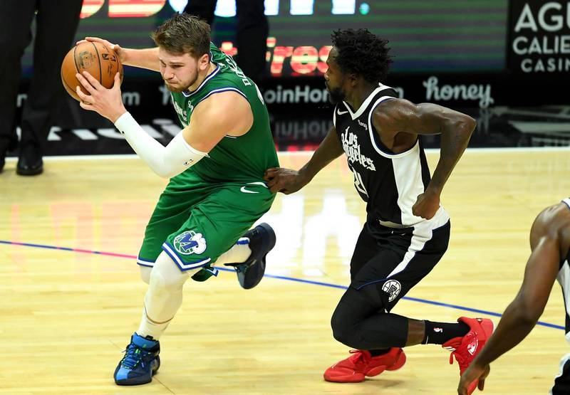 Dec 27, 2020; Los Angeles, California, USA;   Dallas Mavericks guard Luka Doncic (77) is fouled by Los Angeles Clippers guard Patrick Beverley (21) as he drives to the basket in the second half at Staples Center. Mandatory Credit: Jayne Kamin-Oncea-USA TODAY Sports