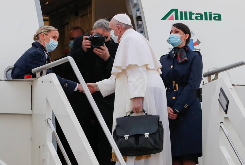 Pope Francis is welcomed by crew members as he boards a plane for his visit to Iraq at Leonardo da Vinci-Fiumicino Airport in Rome, Italy, March 5, 2021. REUTERS/Remo Casilli