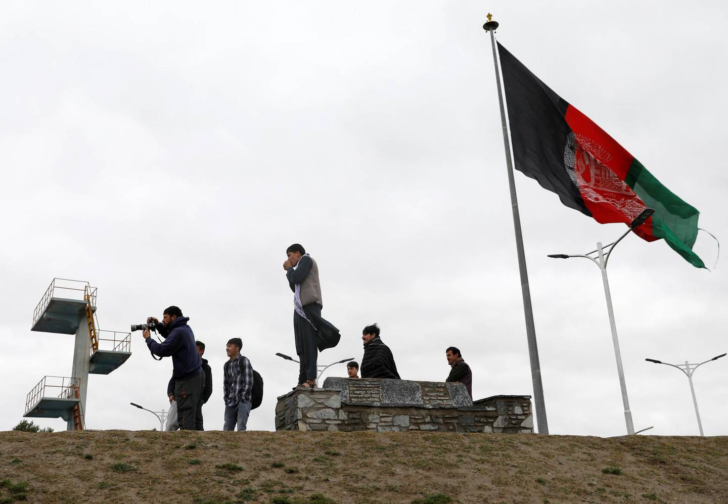 Youths take pictures next to an Afghan flag on a hilltop overlooking Kabul, Afghanistan, April 15, 2021. REUTERS/Mohammad Ismail