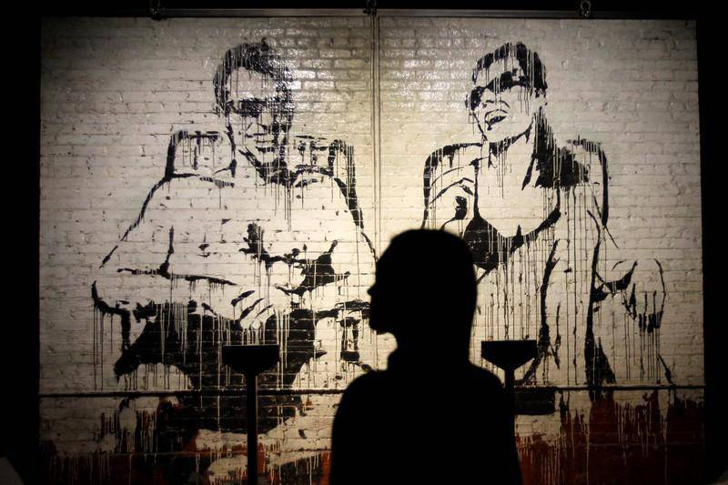 epa07212246 A woman looks at an artwork by British artist Banksy, as she visits the 'unauthorized' exhibition 'Banksy, genious or vandal?' during its opening in Madrid, Spain, 06 December 2018. The exhibition, running from 06 December to 10 March, features, for first time in Spain, some 70 artworks by the street artist.  EPA-EFE/PAOLO AGUILAR