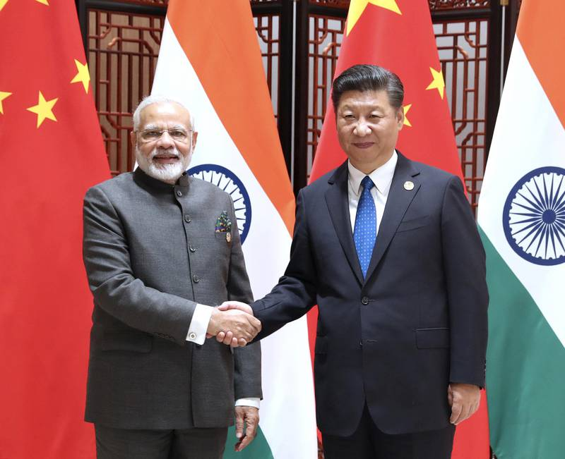 """In this photo released by China's Xinhua News Agency, Indian Prime Minister Narendra Modi, left, and China's President Xi Jinping shake hands as they pose for a photo during a meeting on the sidelines of the BRICS Summit in Xiamen in southeastern China's Fujian Province, Tuesday, Sept. 5, 2017. India's foreign secretary says the leaders of China and India have emphasized that peace and tranquility in their border areas is a """"prerequisite"""" for the further development of their relationship. (Ma Zhancheng/Xinhua via AP)"""
