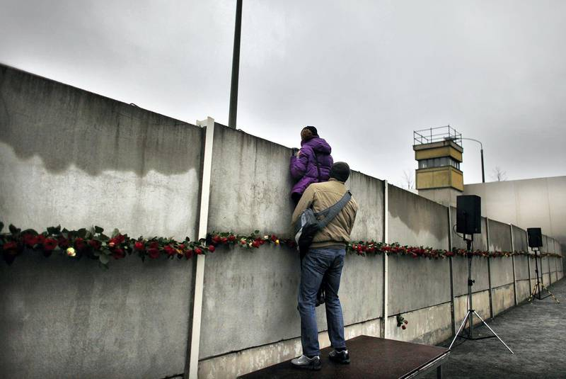 BERLIN - NOVEMBER 09:  A couple attempts to peek through cracks and among roses left by visitors in a still-existing section of the Berlin Wall into the so-called 'death strip,' where East German border guards had the order to shoot anyone attempting to flee into West Berlin, at the Bernauer Strasse memorial on the 20th anniversary of the fall of the Wall on November 9, 2009 in Berlin, Germany. The city of Berlin is celebrating the 20th anniversary of the fall of the Wall, which led to the end of communist rule in East Germany and later on the reunification of East and West Germany, with a spectacular event at the Brandenburg Gate and the participation of international leaders.  (Photo by Carsten Koall/Getty Images)