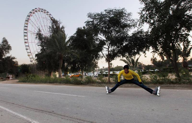 BAGHDAD, IRAQ - DECEMBER 02:  A teenager rollerblades in front of the Ferris wheel at Zawraa Park on December 2, 2011 in Baghdad, Iraq. The 180-foot tall Ferris wheel opened earlier this year and is the second largest in the Middle East. Iraq is transitioning as the U.S. military continues its withdrawal from the country, planning to be completed by the end of December, following the war that began in 2003. (Photo by Mario Tama/Getty Images)