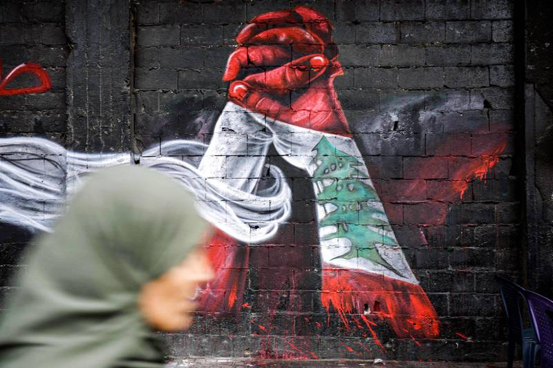 This picture taken on October 24, 2019 in the northern Lebanese city of Tripoli shows a woman passing by graffiti depicting two hands holding each other, both painted in the colours of the Lebanese national flag, painted by Palestinian refugee Ghayath al-Rawbeh, who was originally a Palestinian refugee in Syria and fled with the start of the Syrian crisis, painted on a wall at al-Nour Square in the city centre.  - RESTRICTED TO EDITORIAL USE - MANDATORY MENTION OF THE ARTIST UPON PUBLICATION - TO ILLUSTRATE THE EVENT AS SPECIFIED IN THE CAPTION  / AFP / Ibrahim CHALHOUB / RESTRICTED TO EDITORIAL USE - MANDATORY MENTION OF THE ARTIST UPON PUBLICATION - TO ILLUSTRATE THE EVENT AS SPECIFIED IN THE CAPTION