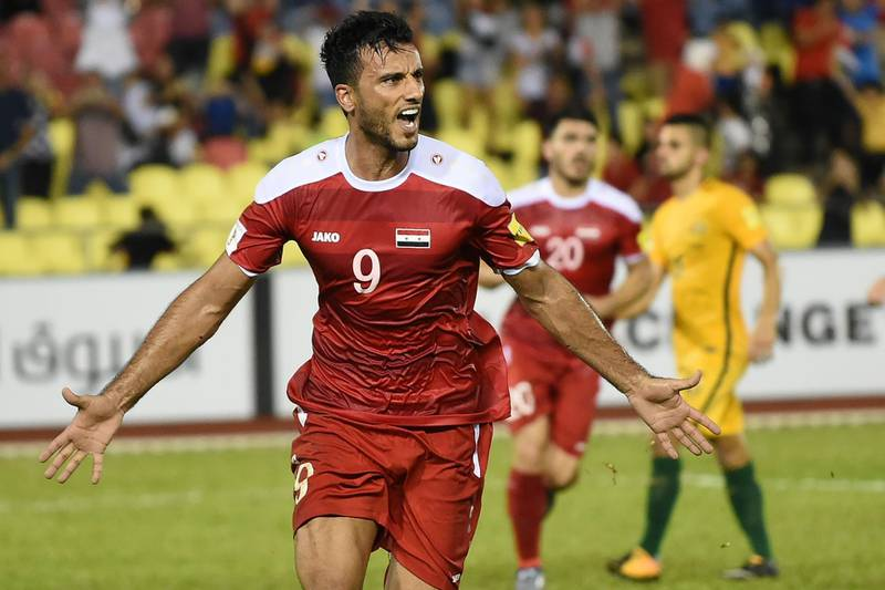 Omar Al Somah of Syria (L) celebrates a penalty goal against Australia during the 2018 World Cup qualifying football match between Syria and Australia at the Hang Jebat Stadium in Malacca on October 5, 2017. / AFP PHOTO / MOHD RASFAN