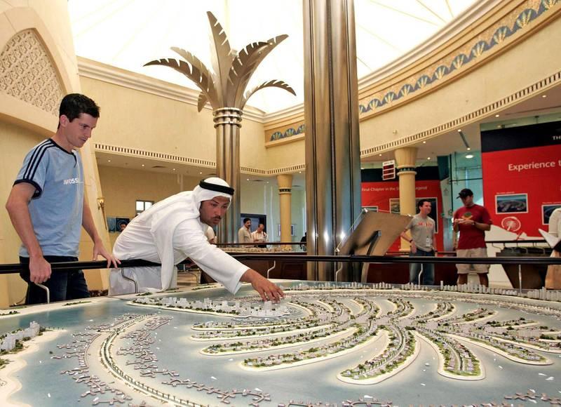 Hamza Mustafa, the executive of an Emirati company, shows British tennis player Tim Henman (R) the Palm Island project model in Dubai 21 February 2005. Henman is in the UAE to participate in the Dubai Open.     AFP PHOTO/JORGE FERRARI (Photo by JORGE FERRARI / AFP)