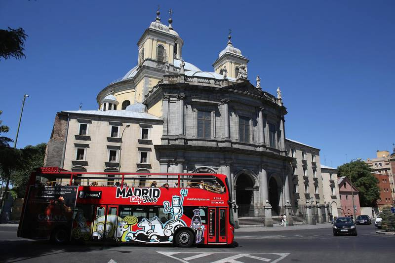 MADRID, SPAIN - JULY 07:  Tourists ride a sightseeing bus past the Basilica de San Francisco el Grande on July 7, 2012 in Madrid, Spain. Despite having the fourth largest economy in the Eurozone, the economic situation in Spain remains troubled with their unemployment rate the highest of any Eurozone country. Spain is currently administering billions of euros of spending cuts and tax increases in a bid to manage its national debt. Spain also has access to loans of up to 100 billion euros from the European Financial Stability Facility which will be used to rescue the country's banks that have been badly affected by a crash in property prices.  (Photo by Oli Scarff/Getty Images)