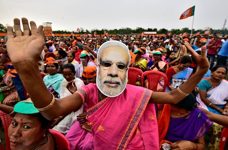 FILE PHOTO: A woman wearing a mask of Prime Minister Narendra Modi dances as she attends an election campaign rally being addressed by India's ruling Bharatiya Janata Party (BJP) President Amit Shah at Ahatguri village in Morigaon district in the northeastern state of Assam, India, April 5, 2019. REUTERS/Anuwar Hazarika/File Photo