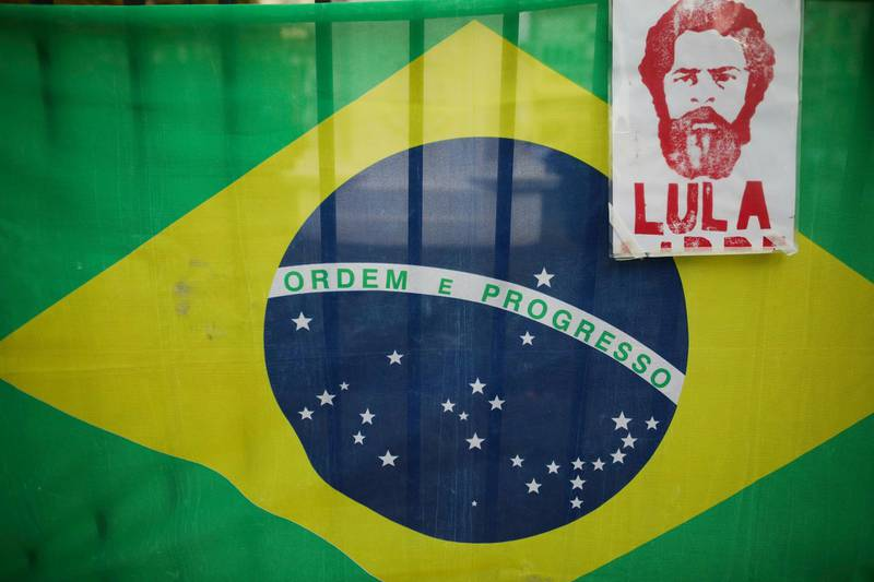 The image of Brazils jailed former president Luiz Inacio Lula da Silva with a Brazilian flag behind it hangs from a fence at Plaza de Mayo, during a protest against the visit of Brazil's President Jair Bolsonaro to Argentina, in Buenos Aires, Thursday, June 6, 2019.(AP Photo/Natacha Pisarenko)