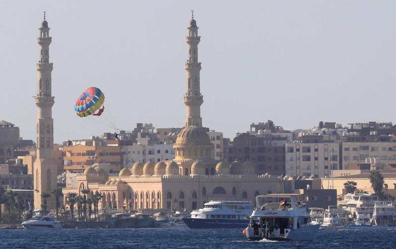 Tourists parasail over the sea in front of the Port Grand Mosque during a summer vacation on the Orange beach at a Red Sea resort, amid the coronavirus disease (COVID-19) pandemic, in Hurghada, Egypt August 25, 2020. REUTERS/Amr Abdallah Dalsh