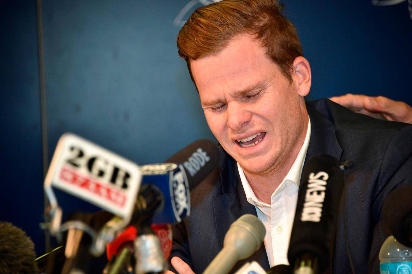 """(FILES) A file photo taken on March 29, 2018 show Australian cricket player Steve Smith reacting at a press conference at the airport in Sydney, after returning from South Africa.   Smith admitted on June 4, 2018 he cried for four days after a ball-tampering scandal in South Africa that rocked the sport, as he told children """"it's okay to show emotion"""". -   / AFP / Peter PARKS"""