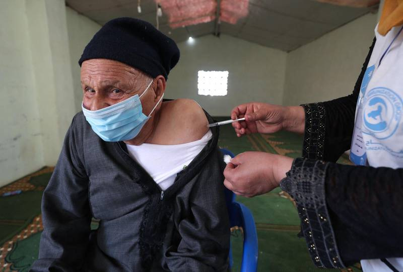 """A medic from the """"Syria Immunization Group"""" NGO administers the COVID-19 AstraZeneca vaccine to a patients with chronic diseases, at a camp for the internally displaced near Marret Misrin town, in the north of Syria's rebel-held Idlib governorate, on June 14, 2021. / AFP / OMAR HAJ KADOUR"""