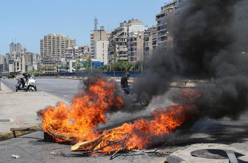 epa09279339 A roadblock made of garbage bins and burning tires during a general strike, in Beirut, Lebanon, 17 June 2021. The strike was called by the General Labor Union in all Lebanese governorates to protest against the country's political and economic crisis amid constant power cuts, the high cost of living and the low purchasing power of the Lebanese pound, as well as the failure of political leaders to form a government after months of deadlock.  EPA/NABIL MOUNZER