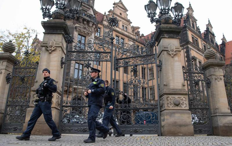 (FILES) This file photo taken on November 27, 2019 shows policemen leaving the Residenzschloss Royal Palace that houses the historic Green Vault (Gruenes Gewoelbe) in Dresden, eastern Germany, days after a spectacular heist. German police on December 14, 2020 arrested a fourth suspect man over the spectacular heist in which more than a dozen diamond-encrusted items were snatched from the Green Vault state museum in Dresden. - Germany OUT  / AFP / dpa / Robert Michael