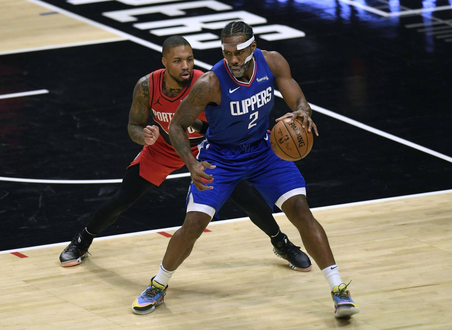 LOS ANGELES, CALIFORNIA - DECEMBER 30: Damian Lillard #0 of the Portland Trail Blazers guards Kawhi Leonard #2 of the LA Clippers during the first half at Staples Center on December 30, 2020 in Los Angeles, California. NOTE TO USER: User expressly acknowledges and agrees that, by downloading and/or using this photograph, user is consenting to the terms and conditions of the Getty Images License Agreement.   Harry How/Getty Images/AFP == FOR NEWSPAPERS, INTERNET, TELCOS & TELEVISION USE ONLY ==