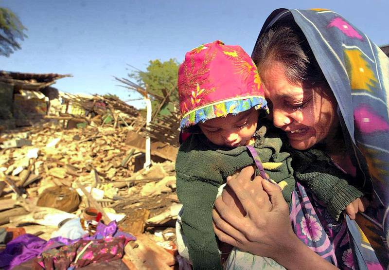 A woman clutches her daughter as she cries in front of the ruins of her house in Bound village in Bhuj district in the western Indian state of Gujarat, 27 January 2001, after an earthquake measuring 6.9 on the Richter scale struck north western India, 26 January 2001, rendering thousands homeless. At least 5000 people are feared dead as a result of the tremor, with casualties expected to rise.  AFP PHOTO/Arko DATTA (Photo by ARKO DATTA / AFP)