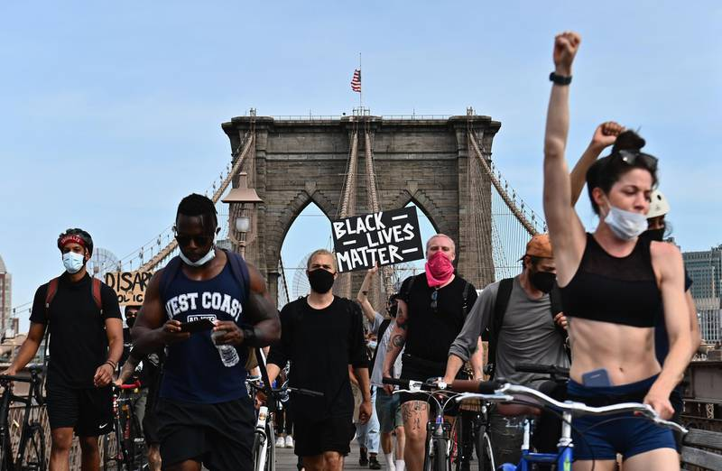 TOPSHOT - Protesters gather to demonstrate the death of George Floyd on June 4, 2020 on top of the Brooklyn Bridge in New York. On May 25, 2020, Floyd, a 46-year-old black man suspected of passing a counterfeit $20 bill, died in Minneapolis after Derek Chauvin, a white police officer, pressed his knee to Floyd's neck for almost nine minutes. / AFP / Angela Weiss