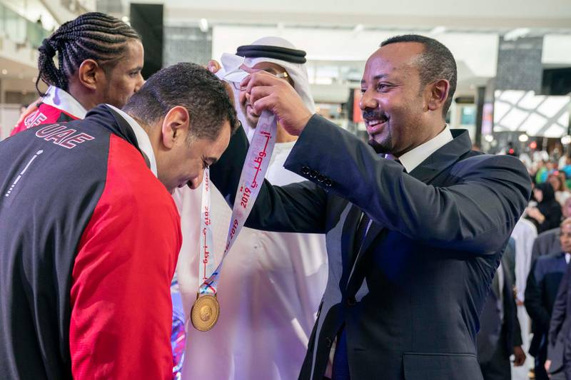 ABU DHABI, UNITED ARAB EMIRATES - March 18, 2019: HE Abiy Ahmed, Prime Minister of Ethiopia (R) presents a medal to an athlete during the Special Olympics World Games Abu Dhabi 2019, at Abu Dhabi National Exhibition Centre (ADNEC).  ( Ryan Carter / Ministry of Presidential Affairs )? ---