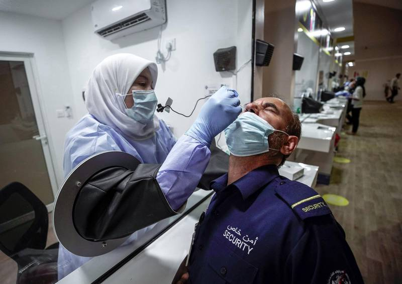 Abu Dhabi, United Arab Emirates, May 6, 2020. the new Ambulatory Healthcare Services, a SEHA Health System Facility, National Screening Project in Mussafah Industrial Area in Abu Dhabi.  --  A swab test is conducted on a security guard.Victor Besa / The NationalSection:  NAReporter:  Nick Webster