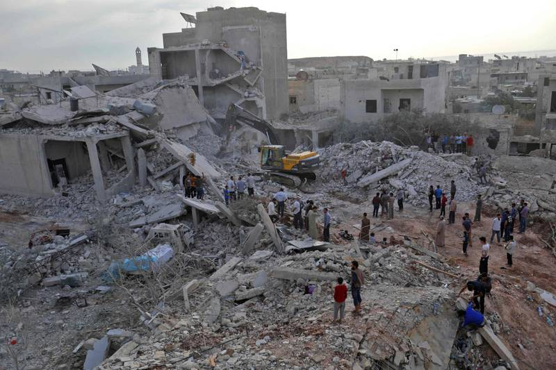 Syrians gather amidst destruction in Zardana, in the mostly rebel-held northern Syrian Idlib province, in the aftermath of following air strikes in the area late on June 8, 2018. Air strikes in northwestern Syria, thought to have been carried out by regime ally Russia, killed 28 civilians including four children, a Britain-based monitor said. The raids, which hit a residential zone in the area of Zardana in the northwestern province of Idlib, also wounded 50 people, the Syrian Observatory for Human Rights monitoring group said.  / AFP / OMAR HAJ KADOUR