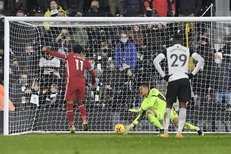 LONDON, ENGLAND - DECEMBER 13: Mohamed Salah of Liverpool  scores their team's first goal from the penalty spot past Alphonse Areola of Fulham during the Premier League match between Fulham and Liverpool at Craven Cottage on December 13, 2020 in London, England. A limited number of spectators (2000) are welcomed back to stadiums to watch elite football across England. This was following easing of restrictions on spectators in tiers one and two areas only. (Photo by Neil Hall - Pool/Getty Images)