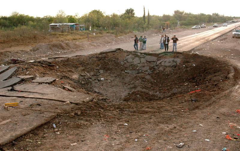 Reporters stand next to a crater, measuring 20 metres (65 feet) in diameter, which was caused by a blast, in a road near Monclova, in the northern state of Coahuila, September 10, 2007. Dozens of people died when a trailer-truck loaded with highly flammable chemicals exploded in a road accident in northern Mexico, local media reported on Monday. REUTERS/Sergio Rodriguez/Zocalo (MEXICO)