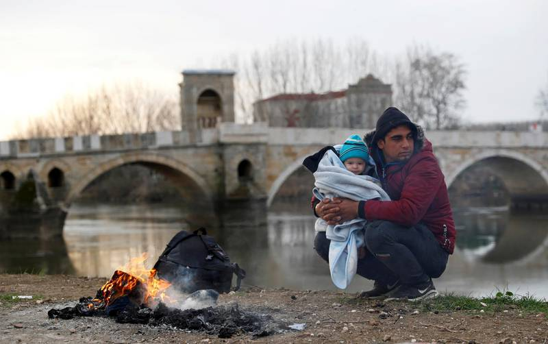 A migrant rests with a child in his arms next to the Tunca river in Edirne, Turkey, March 4, 2020. REUTERS/Leonhard Foeger     TPX IMAGES OF THE DAY