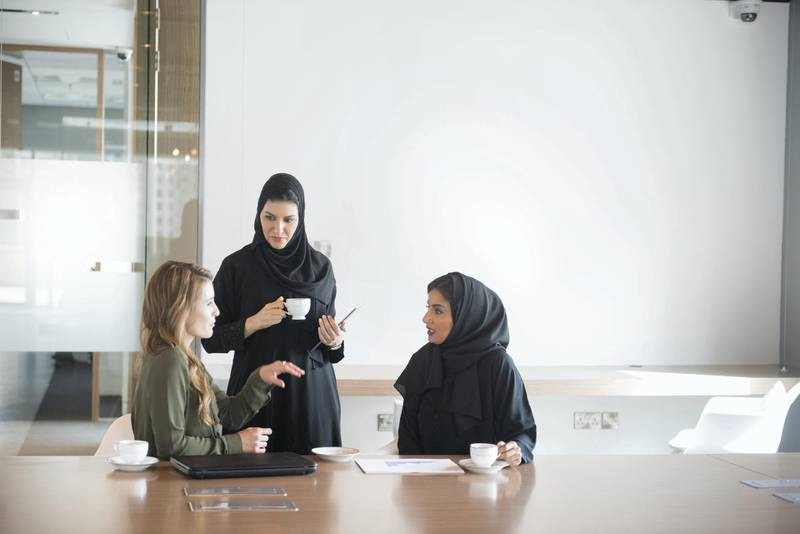 A photo of multi-ethnic businesswomen discussing. Arab Emirati women are in traditional abaya clothes and Caucasian female is in western dress. Professionals are at conference table, in brightly lit modern office discussing business cooperation. Dubai, United Arab Emirates.