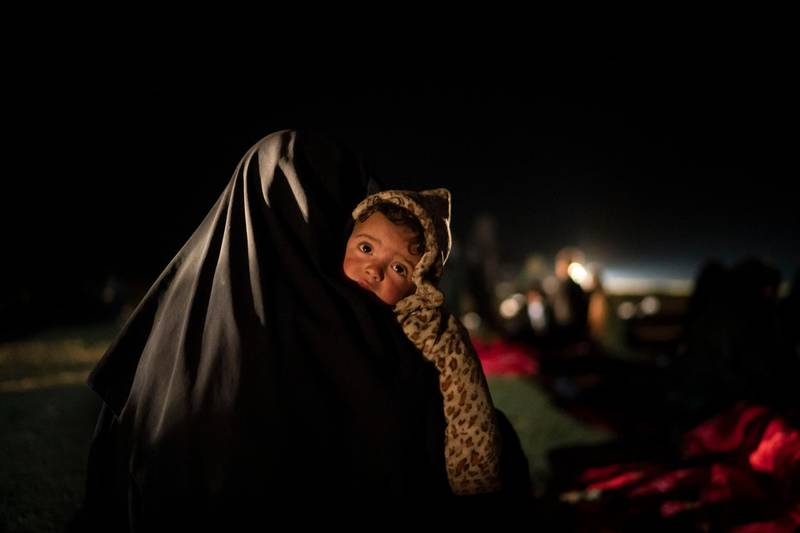 FILE - In this Feb. 25, 2019 file photo, a woman carries her baby at a screening center run by U.S.-backed Syrian Democratic Forces after being evacuated out of the last territory held by Islamic State militants, outside Baghouz, Syria. Hundreds of thousands of Syrians face continued displacement each coming year if the conflict continues and economic conditions further deteriorate, the Norwegian Refugee Council, a prominent humanitarian organization said Monday, March 8, 2021. The Syrian conflict, which marks 10 years later this month, has resulted in the largest displacement crisis since World War II, the council said. (AP Photo/Felipe Dana, File)