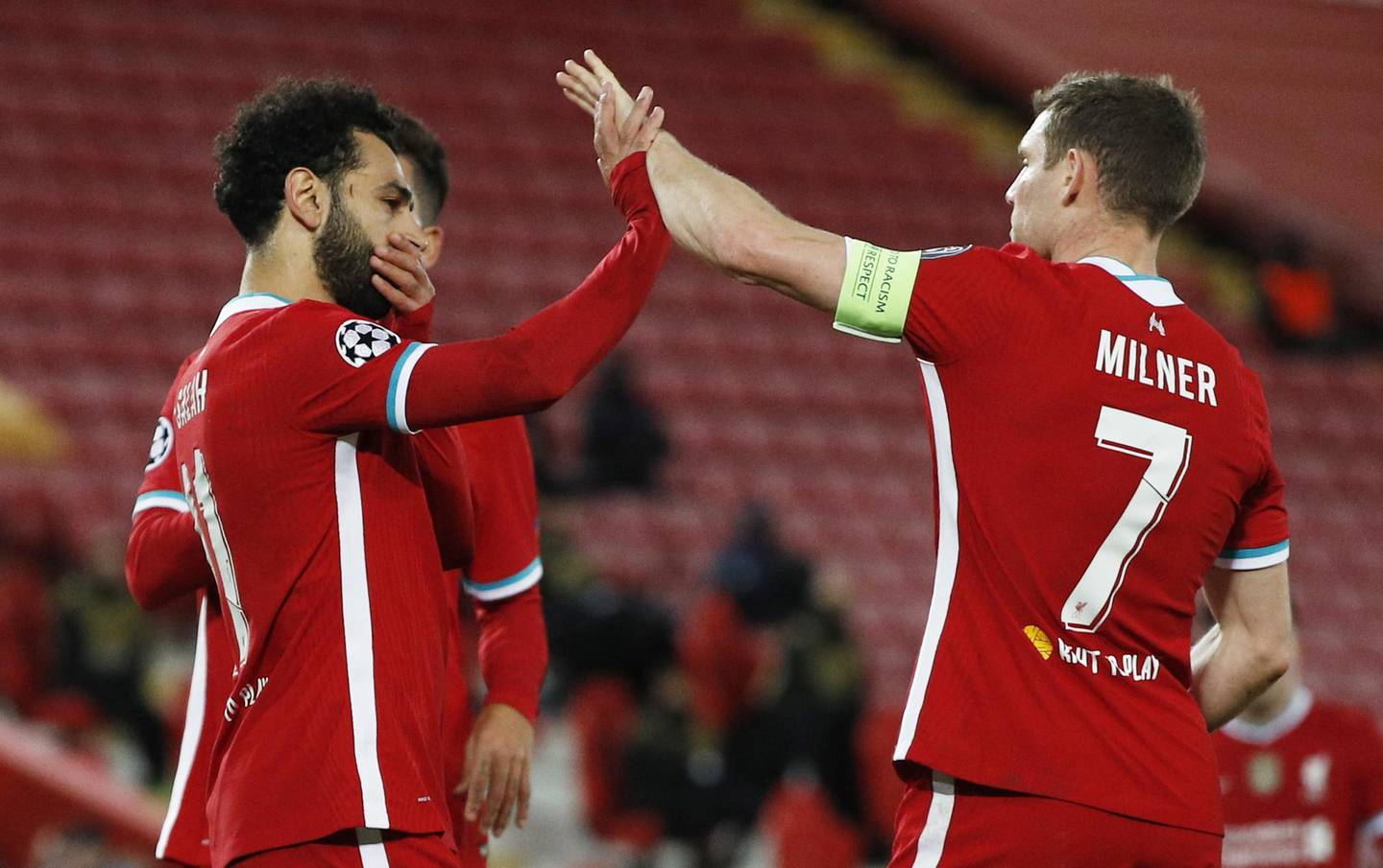 epa08779340 Liverpool's Mohamed Salah (L) celebrates with team mate James Milner after scoring the 2-0 goal during the UEFA Champions League group D match between Liverpool and Midtjylland in Liverpool, Britain, 27 October 2020.  EPA/Phil Noble / POOL